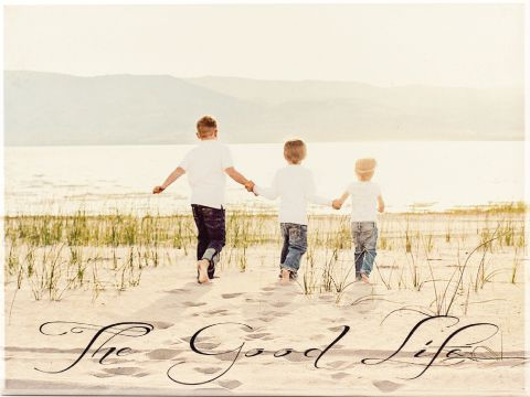 wood photo of three boys playing in the sand next to a lake