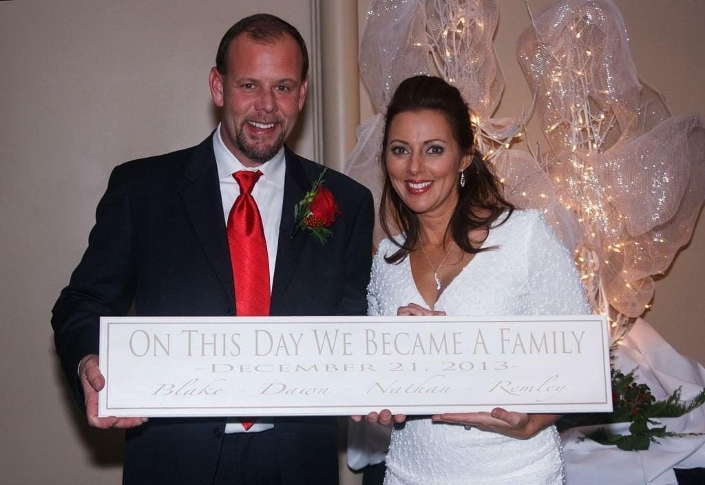 on this day we became a family established sign with bride and groom holding sign for photo