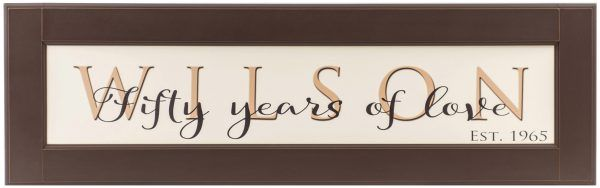 "Personalized wood framed Sign Off white wood sign with tan family name framed in brown wood frame with saying ""Fifty years of love"", and established date in black complete view"