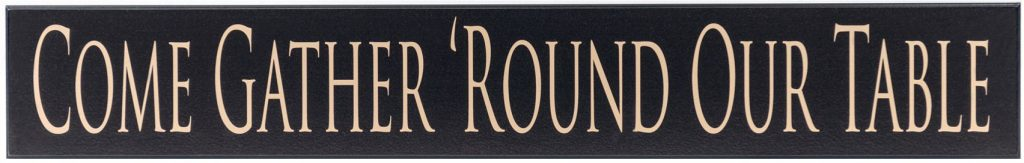 "Black wooden kitchen sign with the text ""Come Gather Round Our Family"" in tan text through the middle of the sign."