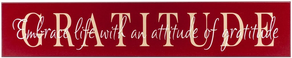 "Red wooden family sign with the word ""Gratitude"" in tan across the front of the sign and the saying, ""Embrace life in the attitude of gratitude"" in off white through the middle of the sign."