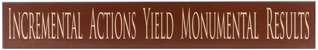 "Chocolate wooden sign with saying, ""Incremental Actions Yield Monumental Results"" in tan through the middle of the sign."