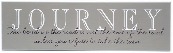 "Charcoal wooden sign with saying, ""Journey-The bend in the road is not the end of the road unless you refuse to take the turn"" in black through the middle of the sign."