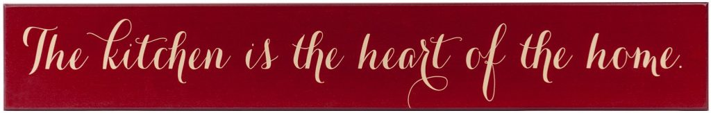"Red wooden kitchen sign with the text ""The Kitchen is the Heart of the Home"" in off white text through the middle of the sign."