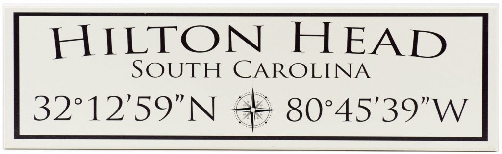 Latitude and Longitude wooden sign with the Hilton Head South Carolina along the top of the sign as well as the latitude and longitude coordinates along the bottom of the sign black text