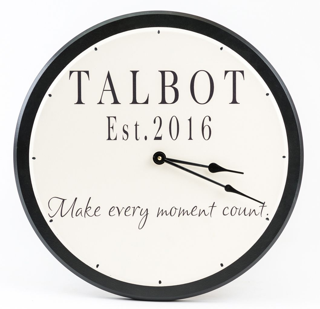 Large personalized wooden wall clock with family name and round black trim with white background.