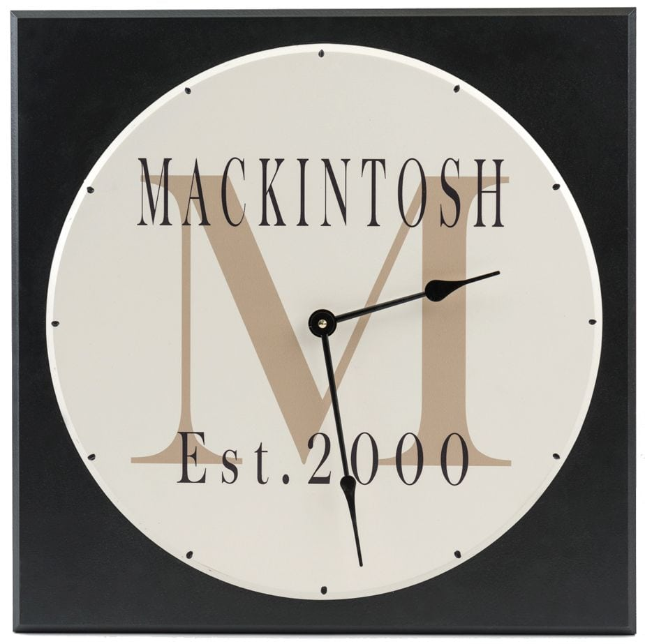 Personalized wooden wall clock with family name and monogram on square black background with tan letter text and family name in black.