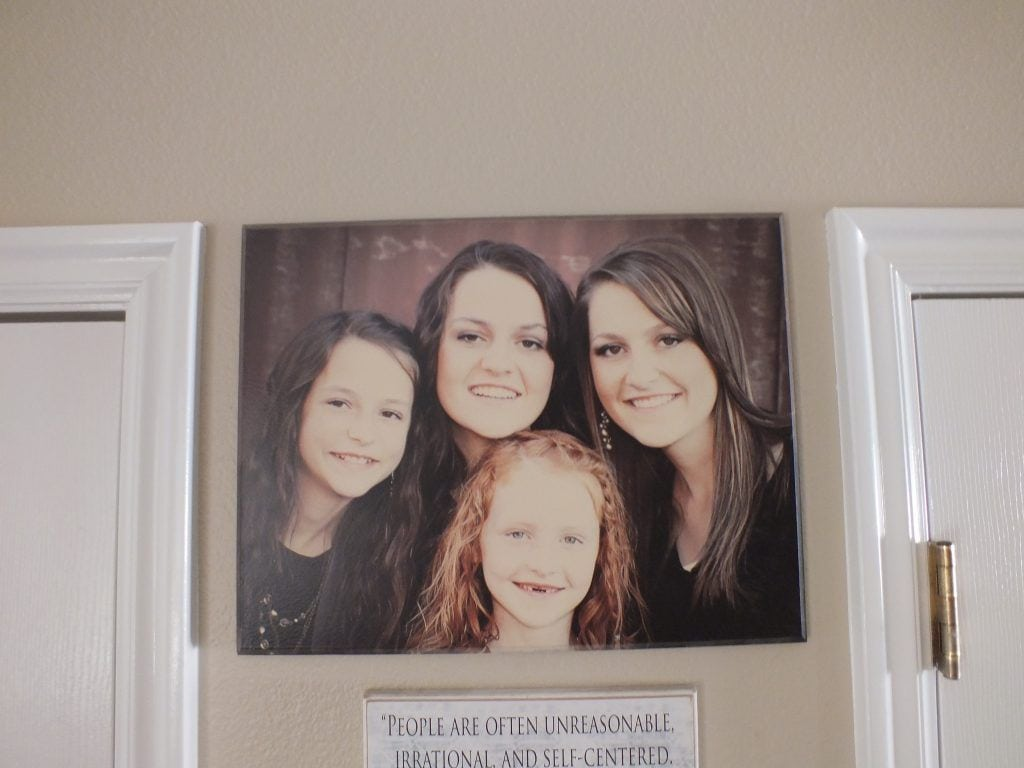 wood photo of four daughters displayed on wall at home