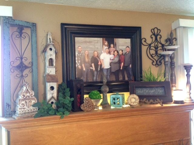 large wood print photo with frame of family above fireplace
