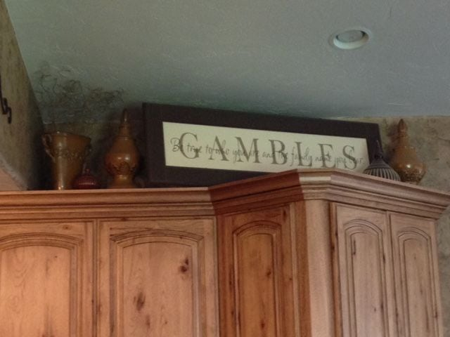 personalized wood black framed sign on top of kitchen cabinet with text